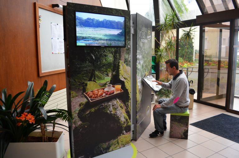 Consultation de l'écran interactif d'un Point i-mobile à Lorient Bretagne Sud.