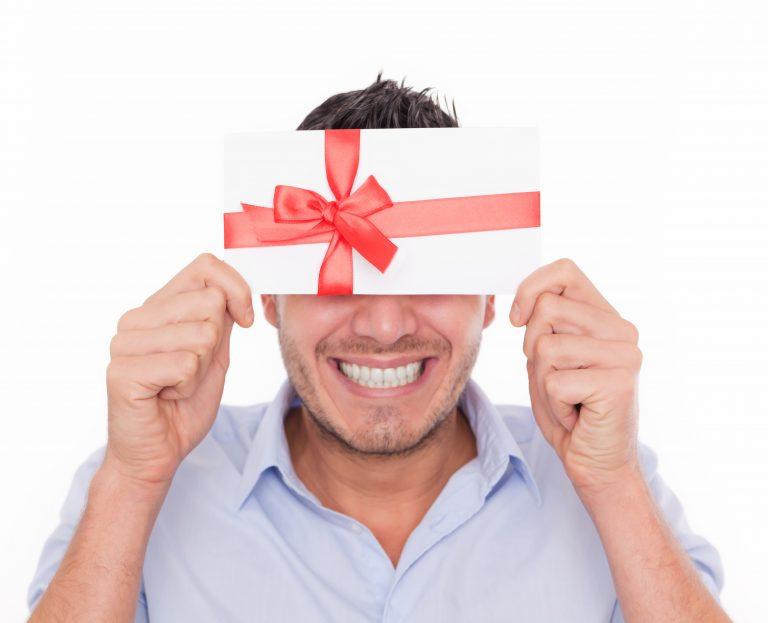 Jeune homme heureux recevant un hèque cadeau