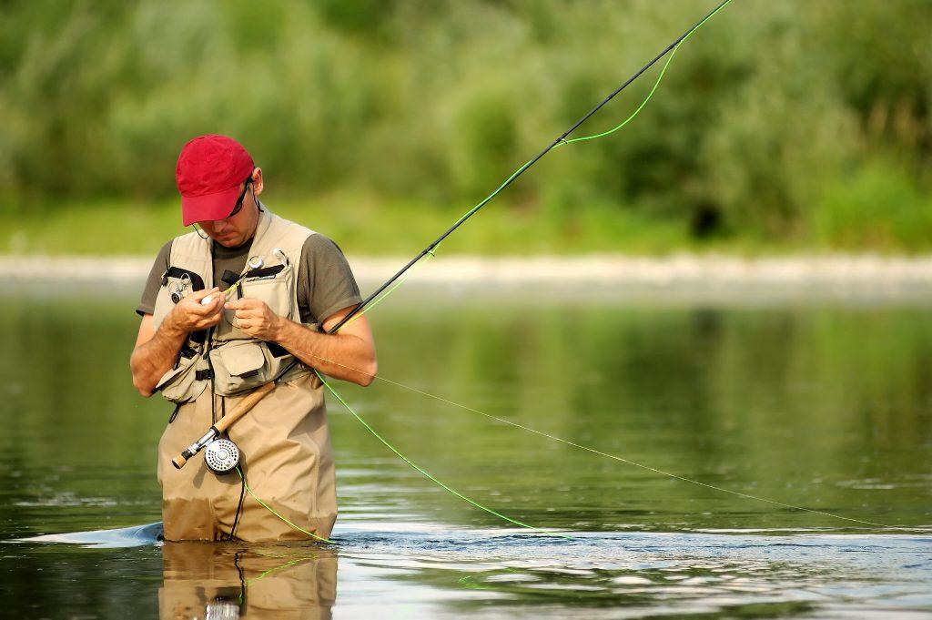 Un pécheur prépare la pêche à la ligne dans la rivière du Scorff.