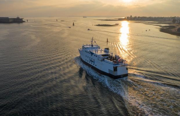 Le bateau de Groix sort de la rade de Lorient en soirée.