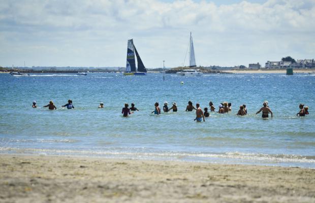 Larmor-Plage, marche aquatique en groupe sur la plage de Toulhars et voiliers au loin.