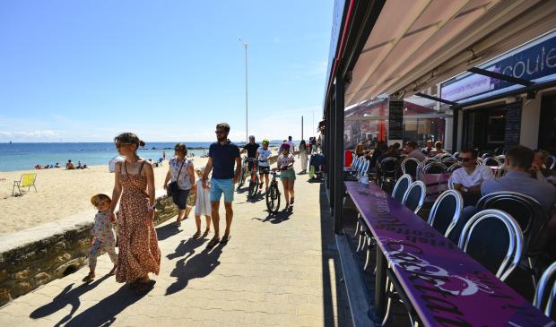 Promeneurs et trrasse de café face à la mer à Port-Maria, Larmor-Plage