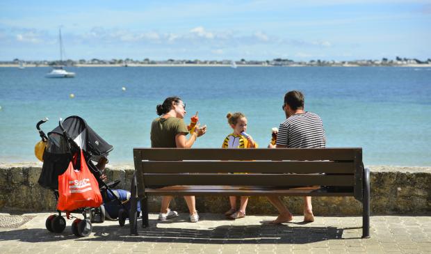 En famille assis sur un banc, se poser et déguster une glace sur la promenade de Port-Maria à Larmor-Plage
