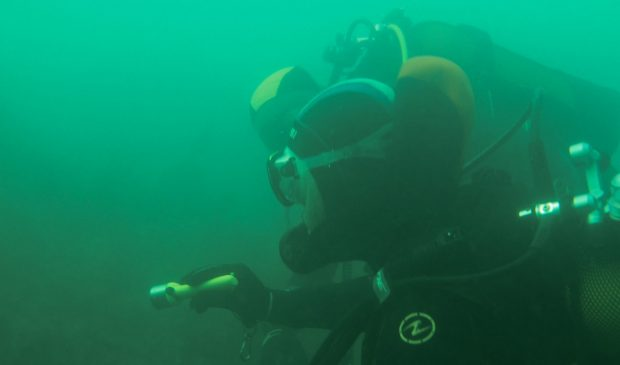 Musée sous-marin à Lorient La Base. Plongeurs sous l'eau, éclairant une épave.