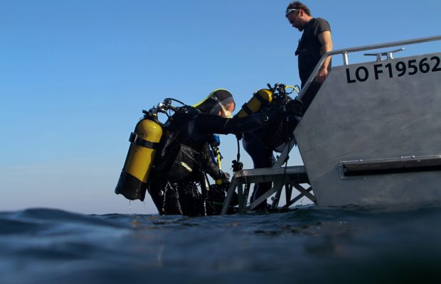 Musée sous-marin à Lorient La Base. Plongeurs entrant dans l'eau depuis le bateau le Kerguelen