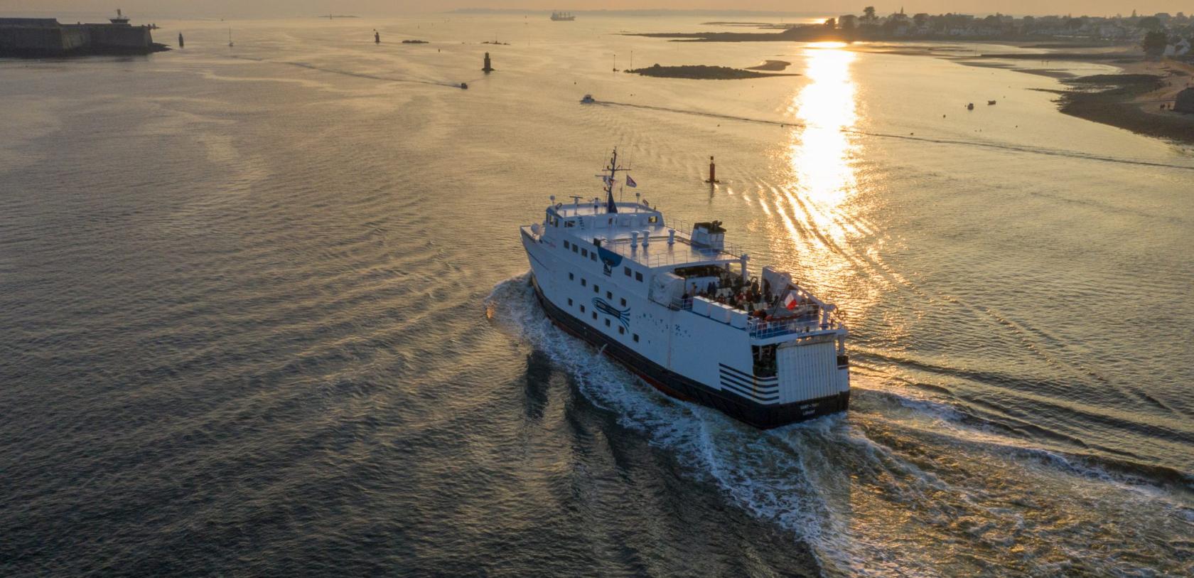 Vue aérienne du bateau de Groix sortant de la rade de Lorient au soleil couchant