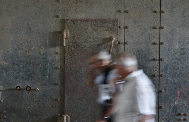 Deux personnes en visite d'un couloir de l'ancienne base de sous-marins à Lorient La Base.